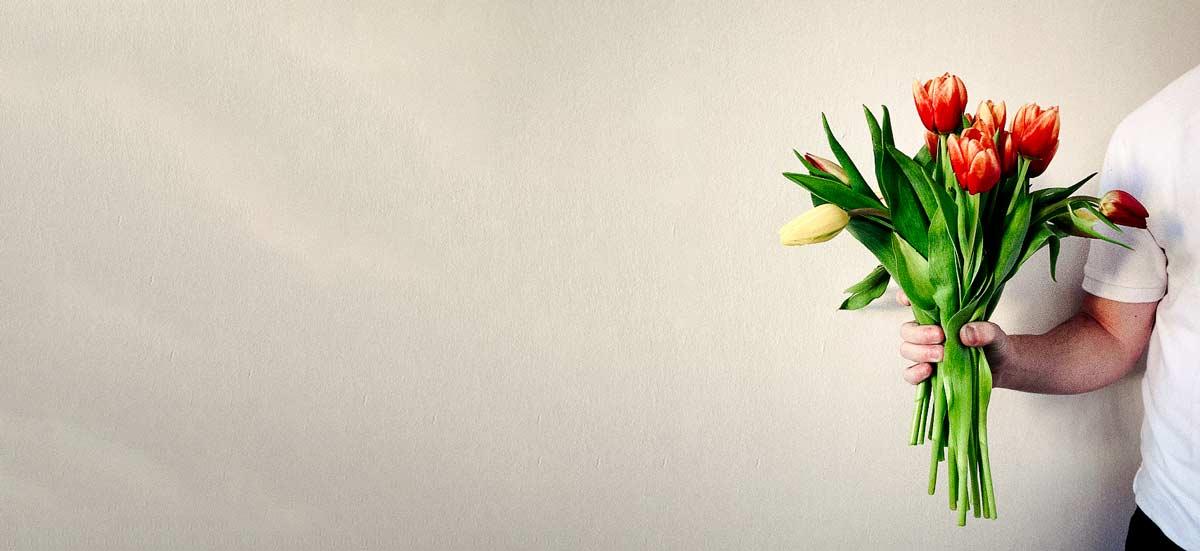 Mužská ruka držící řezané tulipány