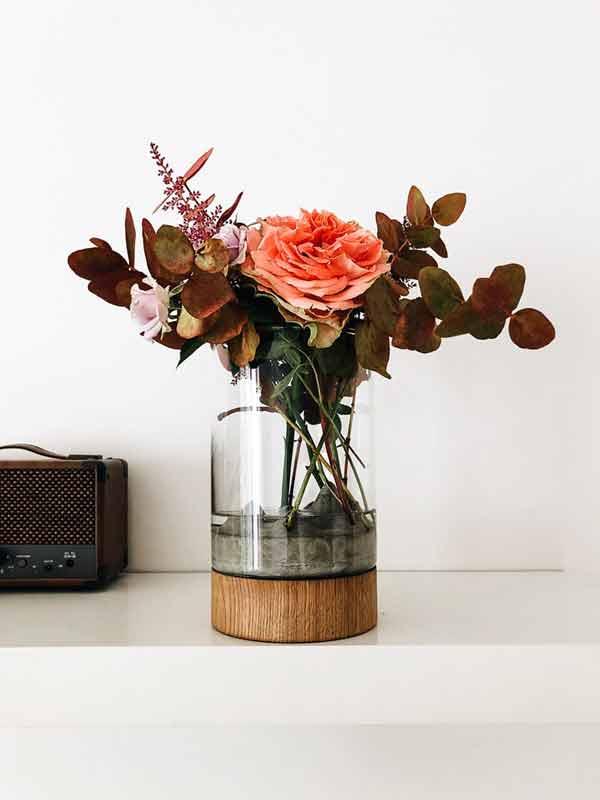 Váza Novaza MOON s květinou na polici s rádiem