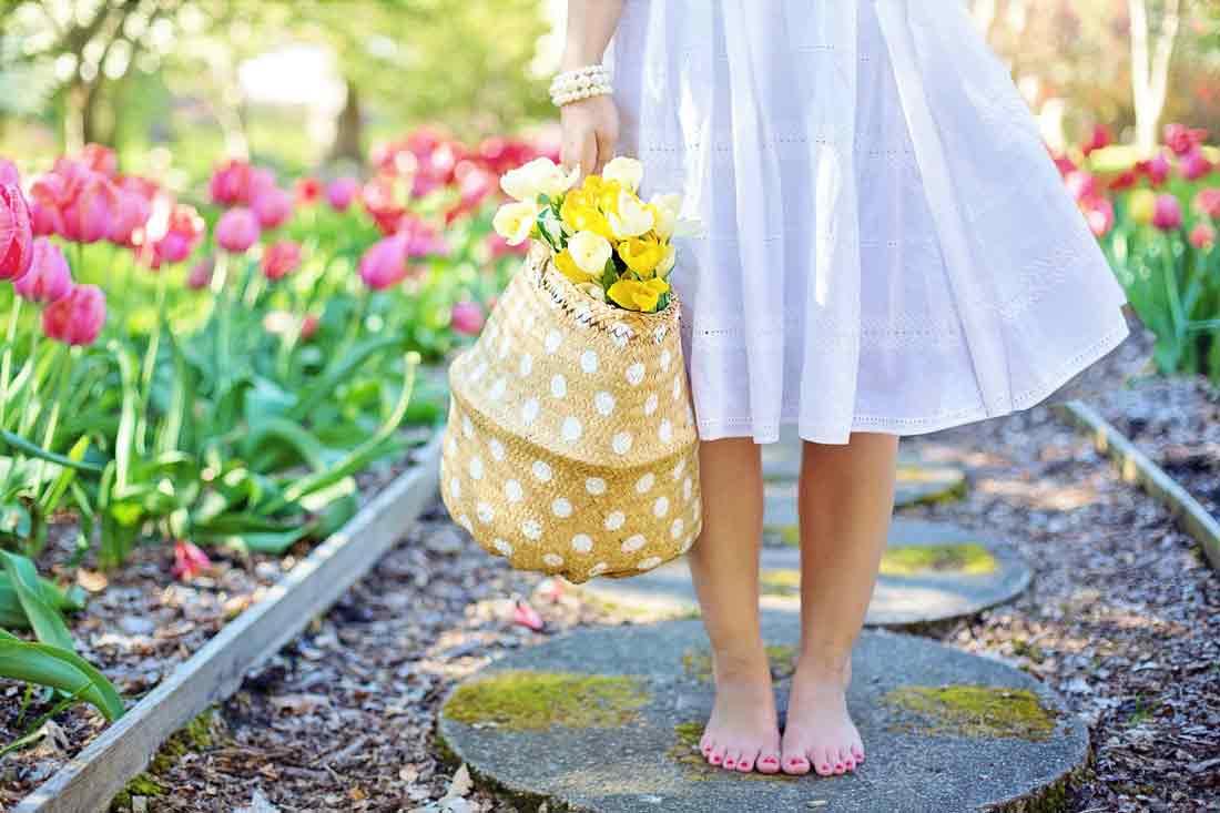 Žena s tulipány v tašce v jarní zahradě
